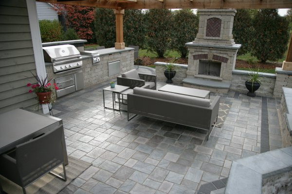 Patio with fireplace and grill island by Unilock with Richcliff paver